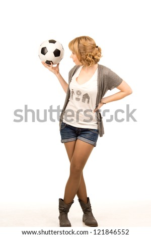 Sexy curvy young blonde woman standing holding a soccer ball balanced on her hand with her head turned to look at it, full length studio portrait on white - stock photo