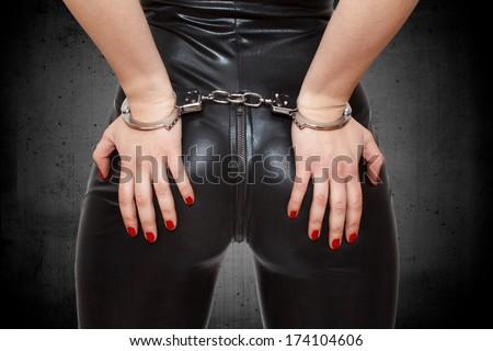 Sexy dominatrix, hands in handcuffs, closeup - stock photo