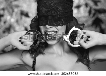 Sexy dominatrix in lace eye cover holding handcuffs, black and white, bdsm - stock photo