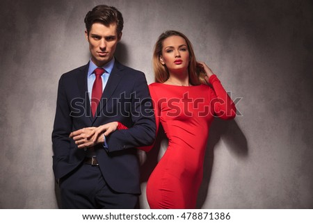 sexy elegant couple holding hands, man in suit and tie, woman in red dress