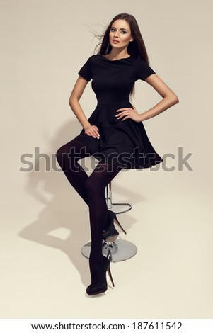 Sexy elegant woman sitting on a chair, long legs, black thighs and high heels - stock photo