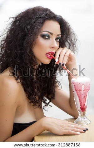 Sexy enchanting playful young woman with curly hair and fashion makeup with bare shoulders looking straight drinking cocktail through straw on white background closeup isolated, vertical picture