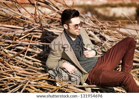 sexy fashion man model dressed elegant holding a bag posing outdoor - stock photo