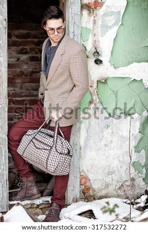 sexy fashion man model dressed vintage elegant holding a bag posing outdoor - stock photo