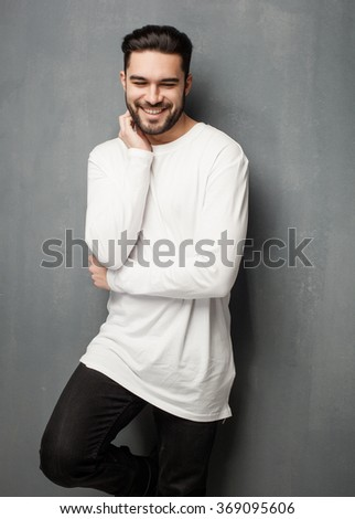 sexy fashion man model in white sweater, jeans and boots smiling - stock photo