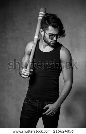 sexy fashion man model with a baseball bat posing dramatic against grunge wall - stock photo
