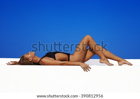 Sexy fashion model in swimwwear with skinny body against blue sky on background
