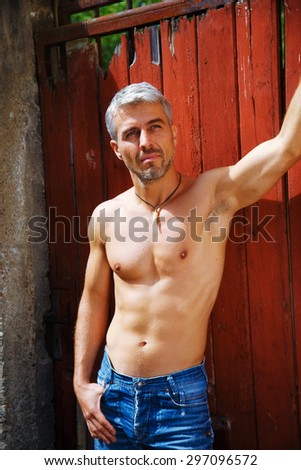 Sexy fashion portrait hot male model in stylish jeans with muscular body posing. Wolves tooth jewelery pendant. - stock photo
