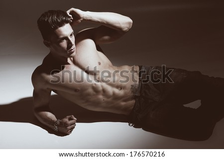 Sexy fashion portrait of a hot male model in stylish jeans with muscular body posing in studio.Glamour colors. - stock photo