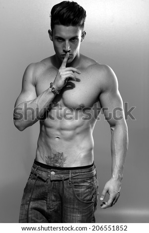 Sexy fashion portrait of a hot male model in stylish jeans with muscular body posing in studio.Glamour photo. B&W.  - stock photo