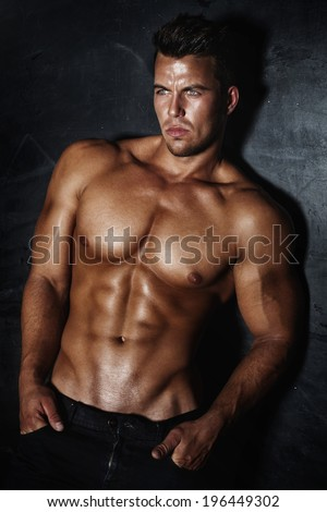 Sexy fashion portrait of a hot male model with muscular body posing in studio, looking at camera. - stock photo