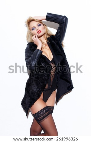 Sexy fashionable blonde woman in underwear and jacket posing at white wall - stock photo