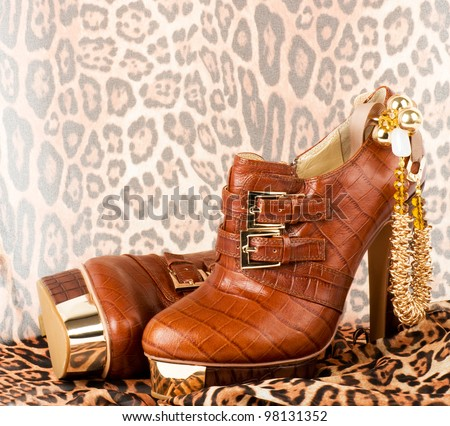 Sexy fashionable shoes with golden jewelry on background. - stock photo