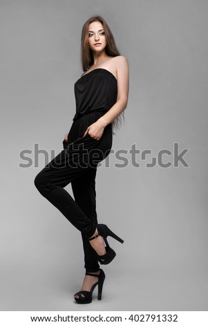 Sexy fashionable young woman posing in a black suit