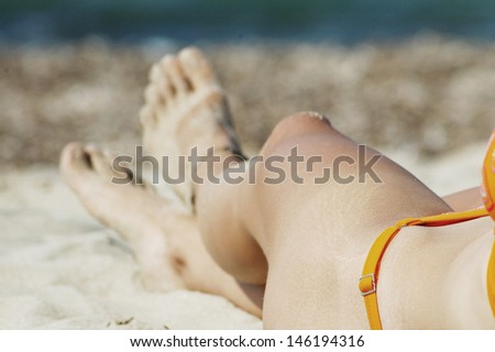 Sexy feet with anklet. Woman relaxing on the beach - stock photo