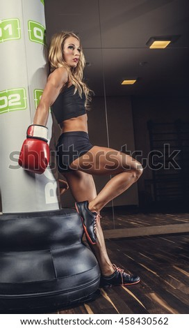 Sexy female boxer posing in fighting club.
