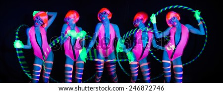 sexy female disco dancer poses in UV costume with hulahoop - stock photo
