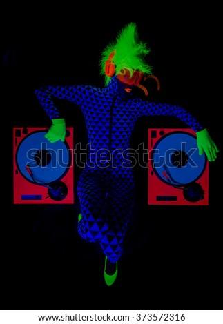 sexy female DJ mixes in a club  in UV fluorescent costume - stock photo