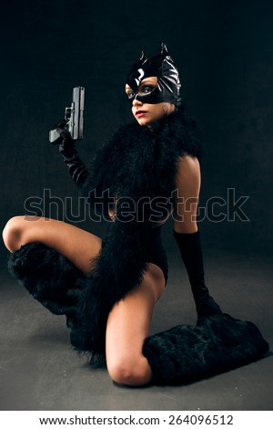 Sexy female dressed as a cat with gun - stock photo