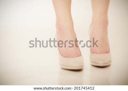 Sexy female feet in beige high heels. Discomfort in new shoes boots. Fashion.