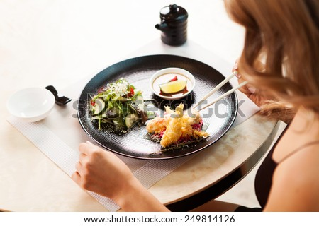 sexy female hands with sticks at restaurant. over shoulder view of beautiful girl eating chinese food - stock photo