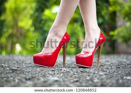 Sexy female  high heeled red shoes  on the way - stock photo