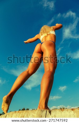 Sexy female in swimwear on the beach under the blue sky. Shot from lower point - stock photo