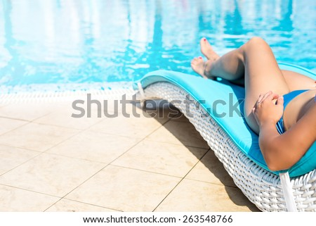 Sexy female legs at blue water of swimming pool - stock photo