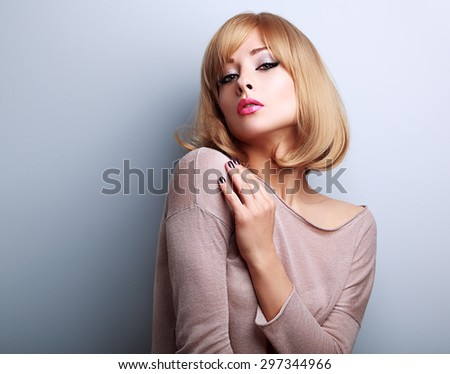 Sexy female model posing with blond short hair style on blue background - stock photo