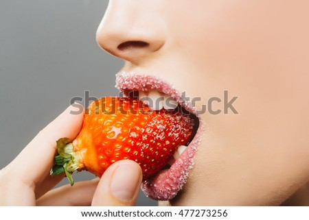 sexy female mouth with sugar lipstick on lips bite red sweet strawberry berry fruit on grey background, closeup