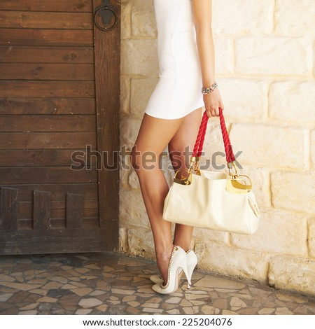 Sexy female shod white high heel shoes holding in a hand fashion bag. - stock photo
