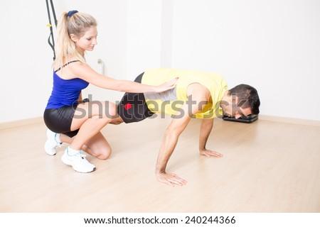 Sexy female trainer explaining suspension training - stock photo
