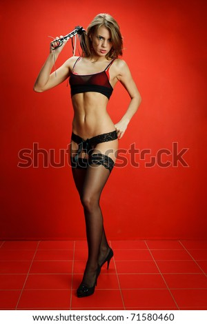 Sexy fetish woman in lingerie with a whip on a red background - stock photo