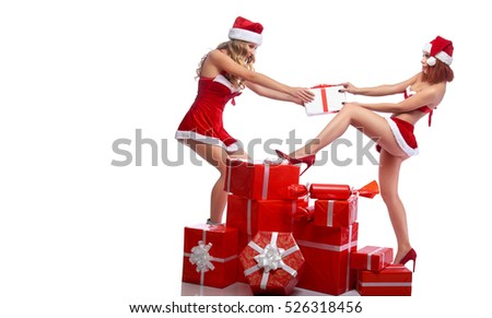 Sexy fighters. Full length shot of two gorgeous sexy girls in Christmas outfits fighting over a Christmas present pulling a gift box isolated copyspace