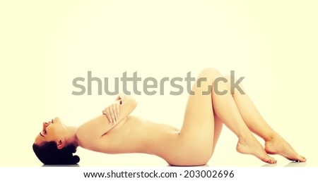 Sexy fit naked woman with healthy clean skin lying down. - stock photo