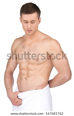 Sexy fit nude man in white towel. Standing isolated over white background
