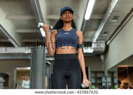 Sexy fitness african american woman working out with dumbbells at the gym - stock photo