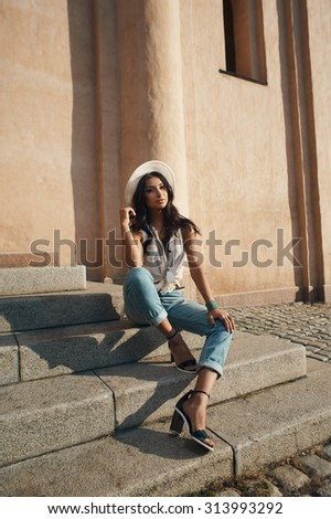 sexy flirting indian lady in jeans, white shirt and white hat against ancient building. She is in harsh morning light. She is positive and playful.  - stock photo