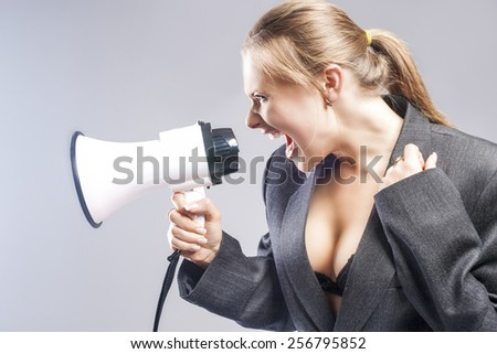 Sexy Furious Caucasian Blond Female in Lingerie and Suite Shouting Using Megaphone. Against Gray Background. Horizontal Image - stock photo