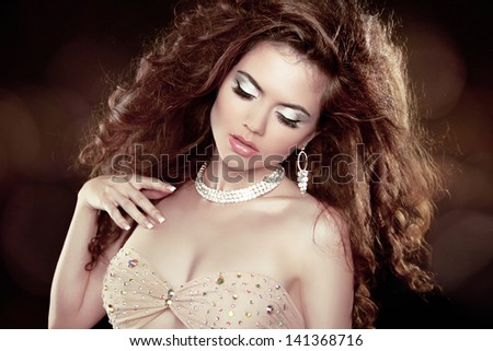 Sexy girl. Beautiful woman with long brown curly hair and makeup. Hairstyle. Jewelry and Fashion. - stock photo
