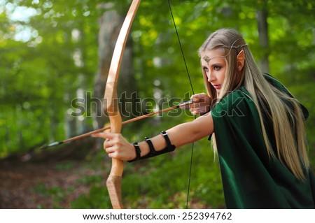 sexy girl elves produces an arrow from a bow - stock photo