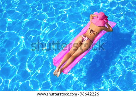 sexy girl floating on a mattress in the sea or swimming pool - stock photo