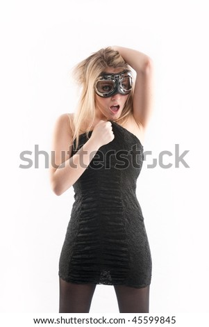 Sexy girl in a black dress wearing goggles and holding up dress with expression isolated on white.