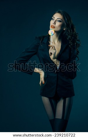 sexy girl in a jacket, stockings and bra sucks a lollipop. vintage toning - stock photo
