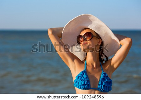 Sexy girl in big hat relaxing on the beach