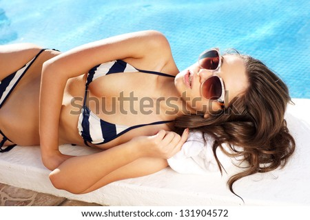 sexy girl in bikini lying near swimming pool. photo from upper point - stock photo