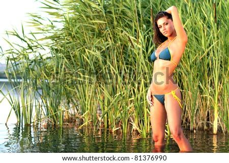Sexy girl in bikini posing at sunset - stock photo