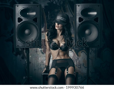 sexy girl in black lingerie and baseball cap sitting on the audio speaker against wall with graffiti - stock photo
