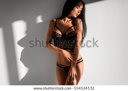 sexy girl in black underwear in bedroom on white background