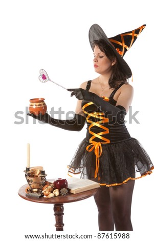 sexy girl in Halloween witch costume prepares a potion